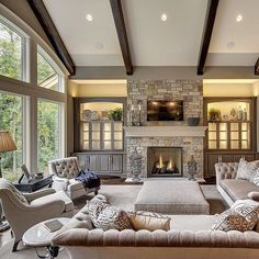 Dark wood coffee table  real stone  tv over fireplace  two story     Warm  inviting and absolutely gorgeous  By Susan Hoffman