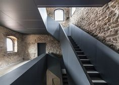 A colossal iron staircase bursts through the stone walls of a medieval tower.