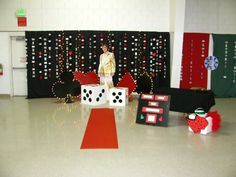 "Another card board and spraypainted sign was created advertising the photo booth and pricing.  We also added a box filled with photo ""props"" like a feather boa, elvis glasses and wig, casino vest, casino visor.  Lastly, a ""red carpet"" was laid down for guests to feel like royalty while walking up to get their photo taken."