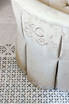 graceful monogram is embroidered in the same color on the back of a dressing table chair