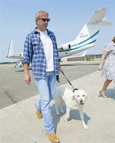 Kevin Costner and his dog Daisy walk on the tarmac of the Executive Flight Centre in Edmonton, Alberta.