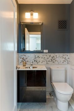 Light sconces adorn this guest bathroom space. A gold vine border serves as the focal point and pairs well with the dark color of the walls.