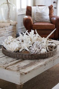 Small round basket filled with assorted shells atop a rustic coffee table