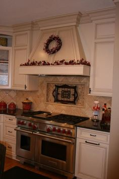 The white cabinetry combined with the eye-catching hoodvent and detailed burnt looking hutch make up an elegant kitchen.
