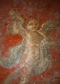 faint remnant of an angel fresco on the wall of a house in Pompeii