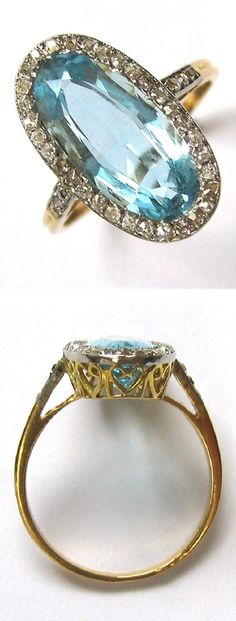 An antique aquamarine and diamond cluster ring, circa 1900. The oval faceted aquamarine estimated to weigh 3.15 carats, claw-set to the centre of a cluster surround of eight-cut diamonds, all white claw-set to a yellow gold mount with fancy heart-shaped scroll pierced gallery, with a fluted yellow gold shank with diamond-set shoulders. #antique #ring