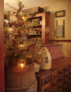 Prim Christmas...old cupboard with drawers & old barrel with prim tree.