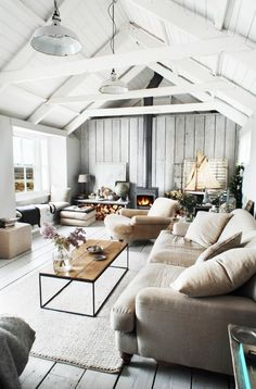 A calming and cool living room with painted white ceilings and exposed ceiling beams