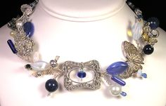 A statement necklace made with a very old rhinestone  shoe buckle  at its center embellished with a sterling silver filigree butterfly, vintage elements, and blue handblown beads, jet and crystal.