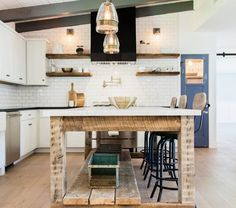 Country kitchen features a white plank sloped ceiling lined with gray wood beams over a reclaimed wood freestanding island topped with white marble lined with industrial counter stools illuminated by Crate and Barrel Morela Glass Pendants.