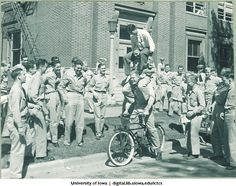 Students performing tricks on a bicycle, University of Iowa, 1940s | Iowa City Town and Campus Scenes | Iowa Digital Library