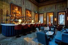 Beautiful bar interior design- love the wood flooring, distressed walls, soft warm lighting, and blue and red color scheme. soho-house-istanbul