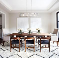 Black and white dining room with Moroccan rug and wooden dining table and chairs.