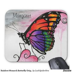 Rainbow Monarch Butterfly Original Fantasy Art Mouse Pad-Monarch butterfly re-imagined with beautiful rainbow colored wings. This fantastical insect sits upon a heart shaped flower in front of a pink and gray sky. This original art piece was created with color pencils for the vibrant colors in the wings and acrylic paint for everything else. Sure to delight the butterfly lover in your life.