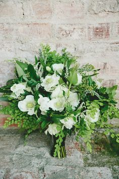 This lush arrangement by florist JL Designs features delicate maidenhair ferns, bay leaf, pieris, double hellebores, anemones, veronicas, and astilbe and is tied with caramel-colored velvet ribbon.