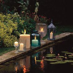 beautiful candles along an outdoor pond