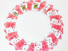 Playing Card Wreath - cute idea, but I would jazz it up a bit! I would make a wreath base, cover it with cards arranged like this, add some black and red feathers, some dice, perhaps? :)