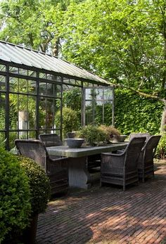 .Love the stone table....could do without the wicker chairs.....love the glass greenhouse!