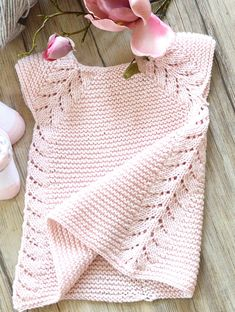 Free Knitting Pattern for Lil Rosebud Baby Dress - This seamless little top down dress / tunic top from OGE Designs is an easy knit, worked in garter stitch with a simple leaf pattern forming the front borders, then cascading down the sides. Sizes, 3 months — 6 months — 12 months — 18 months — 2 years — 4 years — 6 years