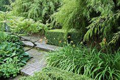 I visningsträdgården på Norrvikens Trädgårdar har små nivåskillnader utnyttjats för att skapa låga trappsteg av marktegel. Växternas former är starka med bladverk som kontrasterar mot varandra. Bonsailiknande fliksumak/Rhus typhina 'Dissecta', bergbambu/Fargesia murieliae, funkior/hosta, dagliljor och buxbom/Buxus sempervirens klippt i räta vinklar.  Spännande i sin enkelhet ...