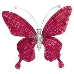 White Gold, Invisibly-Set Ruby and Diamond 'en Tremblant' Butterfly Brooch, Alexis 18 kt., centering a diamond-set body, the 'en tremblant' wings invisibly-set with square-cut and fancy-shaped rubies approximately 38.78 cts., topped by a pair of polished white gold antennae tipped by 2 small round diamonds