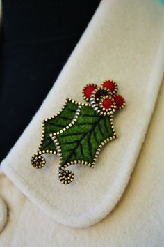 "Felt Holly leaf brooch embellished with pieces of brass zipper and red felt beads.The aprox dimensions   are1 1/2"" x 2 1/2""."