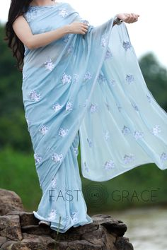Featuring a soft powder blue pure silk chiffon saree with light white ribbonwork floral motifs embroidered all over it. PRICE: INR 18,232.00; USD 268.12 To buy please click here: https://www.eastandgrace.com/products/white-blue-birdies For help reach us at care@eastandgrace.com. With love www.eastandgrace.com