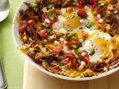 Hashbrown eggs.... WOW      2 tablespoons vegetable oil      8 ounces cooked corned beef, diced      1 white onion, finely chopped      1 bell pepper, finely chopped      2 medium baking potatoes, peeled and shredded (about 2 cups)      4 tablespoons unsalted butter      4 large eggs      Kosher salt and freshly ground pepper      4 slices cheddar cheese (about 2 ounces)