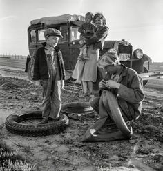"""Fix-a-Flat: 1937 March 1937. """"Migratory agricultural worker family making tire repairs along California highway U.S. 99."""" Photo by Dorothea Lange"""