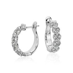 Brilliant and feminne, these diamond hoop earrings feature single brilliant diamonds alternating with diamond pairs set in 18k white gold.