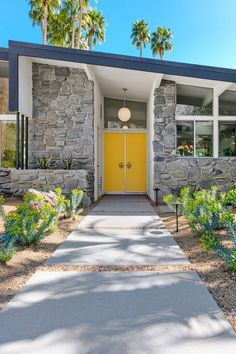 Canary yellow front doors and dark gray roof line compliment the gray rock work in front of house