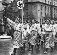 Polish women wearing national costumes saluting officers in a parade.