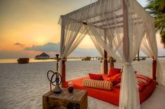 Casual red sofa decorated with curtains on the beach is full of pillows