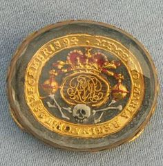 """Queen Mary II Ribbon Slide. The cipher sits on top of tightly woven hair. Beneath that is the skull and crossbones. All around the slide, written in gold, are the words : """"Momento Maria Regina obit 28th Decembris 94."""""""