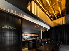 Wooden slats arranged to create a houndstooth pattern cast shadows across this cafe in Dallas which also contains a hidden cocktail bar at the back