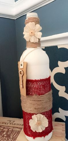 Recycled rustic decorative Wine Bottle painted white embellished with burlap, linen flowers and wooden key. Perfect centerpiece for your house and office. Measurements 11.5 in Tall x 10 in diameter.                                                                                                                                                                                 More
