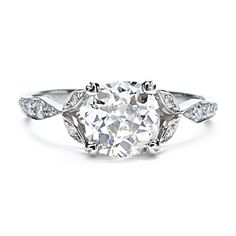 Evoking sentiments from the early 1900's, this hand-detailed engagement ring features an old mine cut cushion-shaped diamond with pave diamond accents.