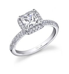 This Magnificent 18K white gold engagement ring features a 1.25 carat Emerald Cut center diamond. Accentuated by surrounding diamonds and diamonds continuing down the sides of the ring totaling 0.42 carats. This diamond engagement ring is available in any shape or size center diamond, in 18K white gold or platinum. All Sylvie Collection diamond engagement rings are available with a flush fit matching wedding band. (For pricing on this diamond engagement ring and other diamond engagement…