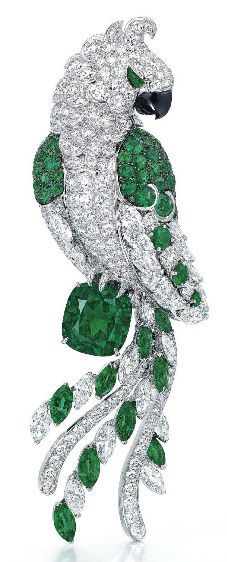 AN EXCLUSIVE EMERALD, DIAMOND AND ONYX BROOCH, BY GRAFF Designed as a pavé-set circular-cut diamond parrot, the wings and tail lined with marquise-cut diamonds with circular and marquise-cut emerald detail, perched on a cushion-shaped emerald, weighing approximately 11.18 carats, further enhanced by an onyx beak, mounted in gold, 10.6 cm  Signed Graff, no. GP10793