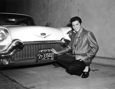 Elvis Presley posing in front of one of his many Cadillacs