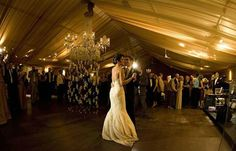 Back lighting behind the sheer drapery adds a dramatic affect to this tented wedding.