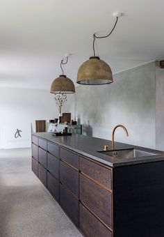 Stylish #kitchen design in dark wood with industrial pendants.