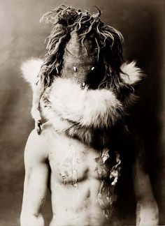 Navajo Ceremonial Costume You are looking at an educational picture of Nayenezgani. It was taken in 1904 by Edward S. Curtis. The picture presents an Indian, facing front, wearing dark mask, fur ruff, paint on torso.
