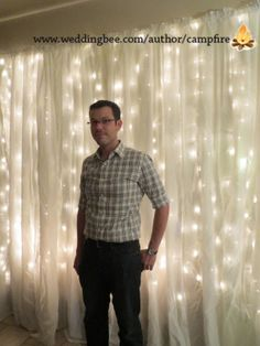 groom in front of string light backdrop