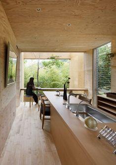 Esta casa de madera en voladizo por el estudio japonés UID Arquitectos se sitúa diez metros sobre el suelo del bosque y tiene un agujero por debajo para permitir que los árboles crezcan en el interior.
