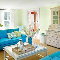 Seafoam green walls provide a fresh backdrop for a pair of bright turquoise sofas and lively throw pillows. The sisal rug grounds the space.