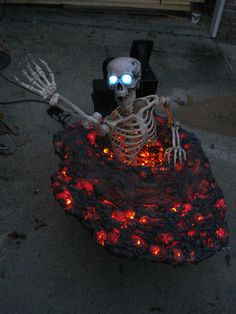 """Skeleton """"Hell Hole"""" Prop. black cheesecloth with red/orange lights under, looks like lava"""