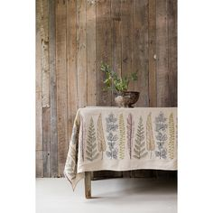 """Inspired by a variety of large leaves and greenery, this tablecloth will add botanical abundance to any home! Measures 70"""" x 90"""" with 2 seams along the solid linen top. Embroidery on 100% linen. Pleas"""