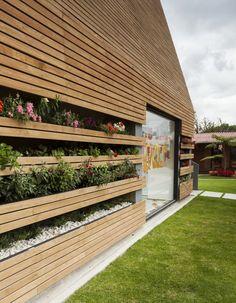 La Leroteca / Lacaja Arquitectos, green wall, garden in wall, flowers on facade, wood exterior wall, kindergarten