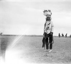 190? Buckwalter portrait of a Cheyenne man wearing a feather headdress, a hairpipe necklace, moccasins, and bells.